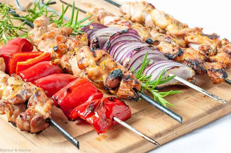 Grilled Rosemary Mustard Chicken Kabobs on a cutting board with skewered peppers and red onions.