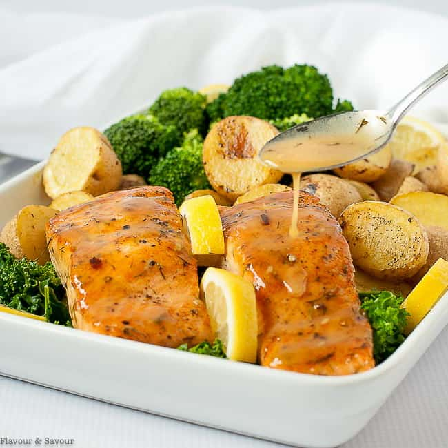 Drizzling glaze from a spoon on Bourbon Maple Glazed Salmon with broccoli