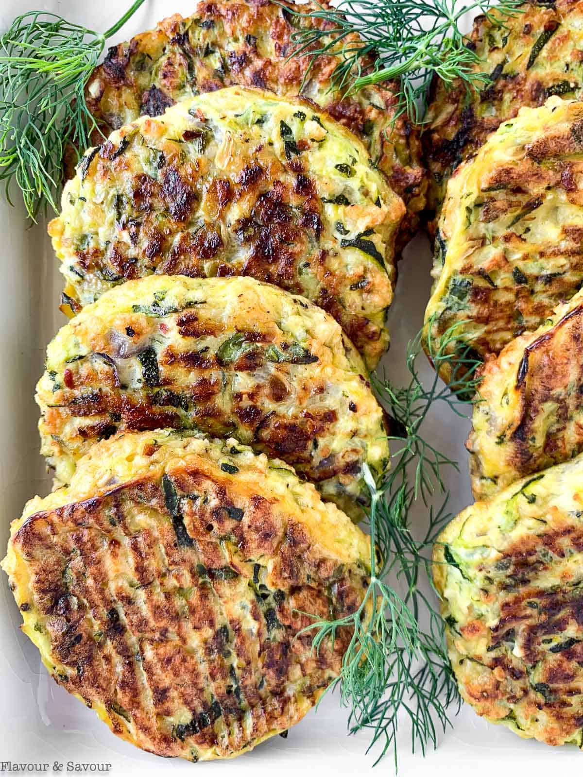 Close up view of 8 zucchini patties on a white platter