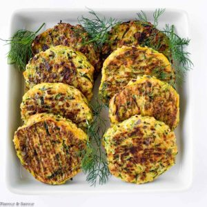8 zucchini patties on a plate with herbs