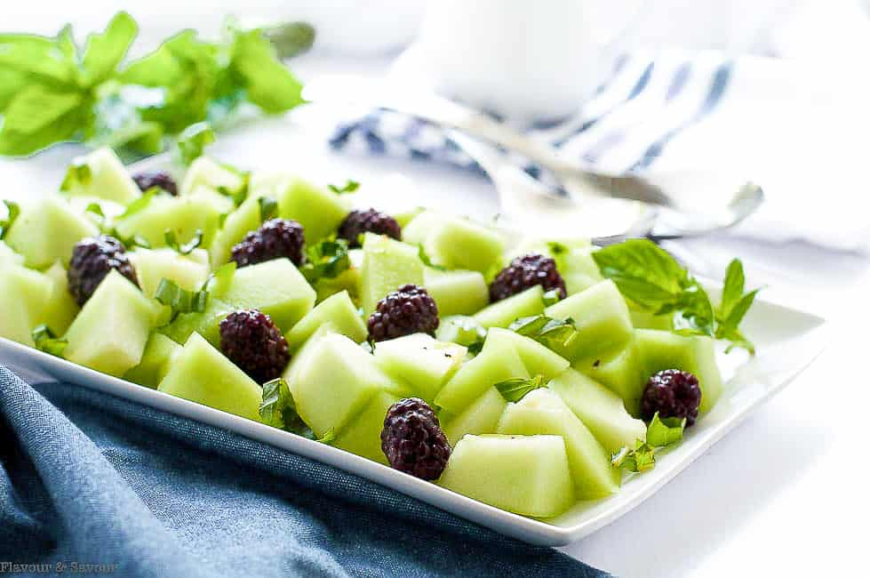 Blackberry Honeydew Melon Salad on a white serving plate with a blue cloth