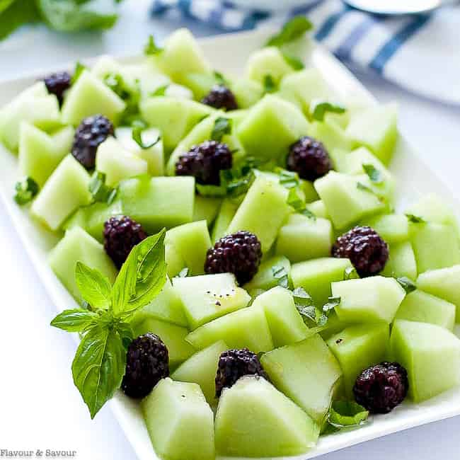 close up view of Blackberry Honeydew Salad with fresh basil leaves