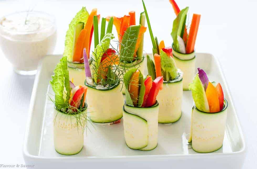 Fresh Veggie Caesar Zucchini Roll-Ups on a white tray.
