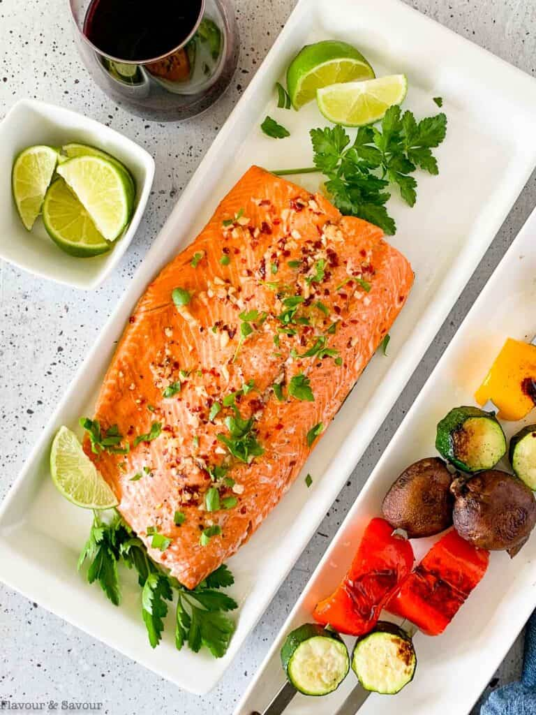 a platter with chili lime salmon filet with lime slices