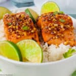 Close up view of two salmon fillets with lime slices on rice