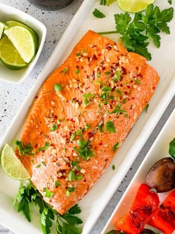 Honey Chili Lime Glazed Salmon on a platter with limes and vegetable kabobs.