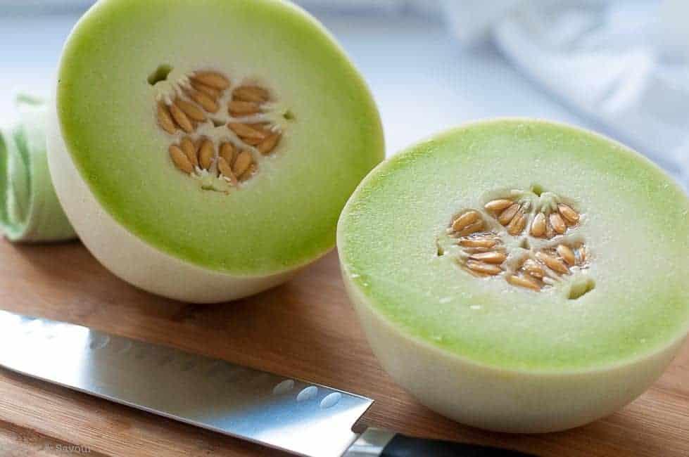 Honeydew Melon sliced in half on a cutting board