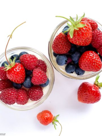 Overhead view of two jars of no bake cheesecake with fresh berries