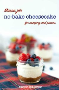 No bake yogurt cheesecake topped with strawberries and blueberries in Mason jars.
