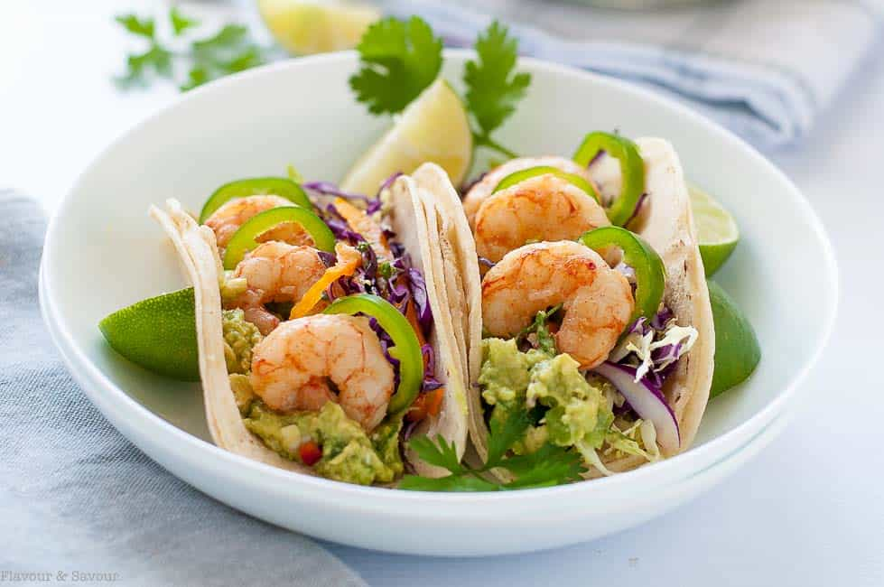 Two Shrimp Tacos with Tomatillo Guacamole and Cilantro Lime Slaw in a shallow white bowl with lime quarters.