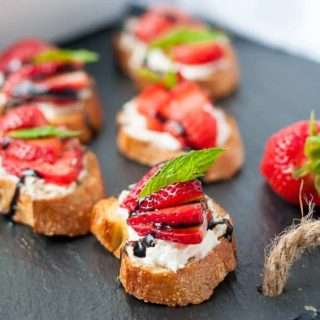Strawberry Whipped Feta Crostini on a black slate board