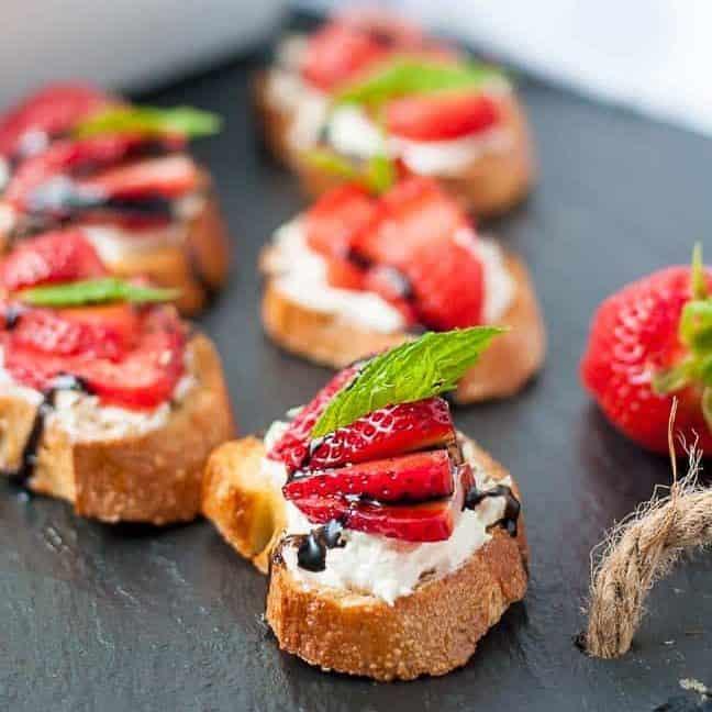 Strawberry Whipped Feta Crostini on a black slate board