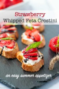 crostini appetizers spread with whipped feta cheese, sliced strawberries and mint leaves on a black slate board