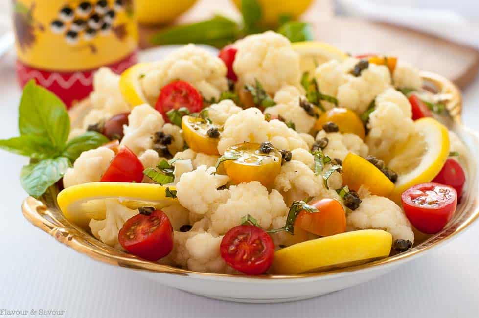 Cauliflower lemon basil salad with toasted capers garnished with tomatoes, lemon slices and fresh basil.