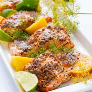 Honey Dijon Glazed Salmon with sprigs of fresh dill and edible flowers