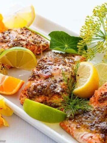 Honey Dijon Glazed Salmon fillets garnished with lemon, lime and orange slices