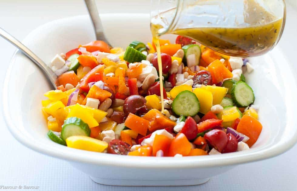 Pouring dressing on Mediterranean Chopped Salad with Cannellini Beans