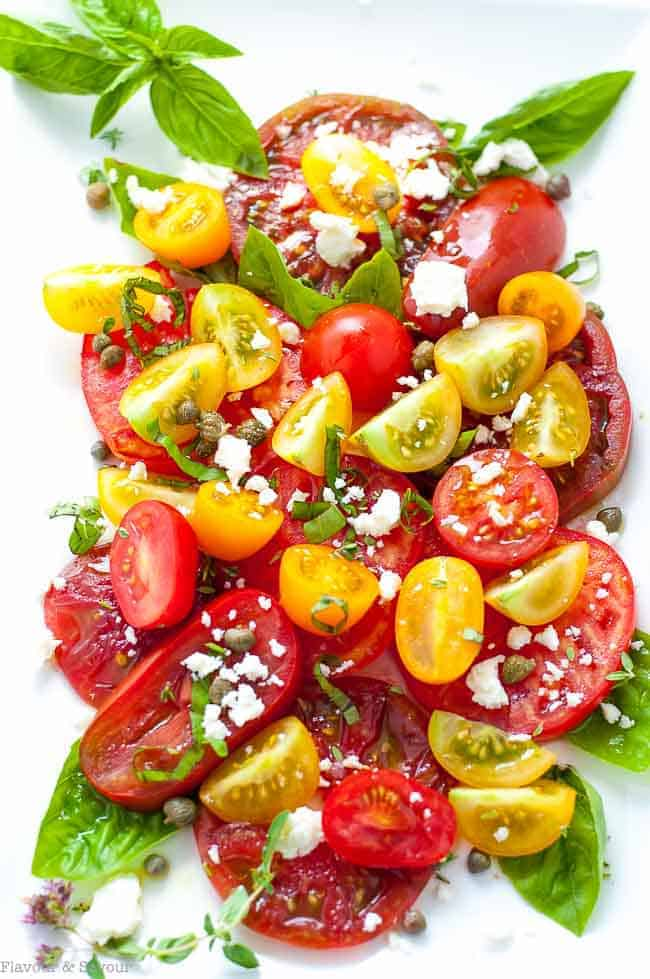Heirloom Tomato Salad with Basil, Capers and Feta. Overhead view garnished with crumbled feta cheese and basil leaves