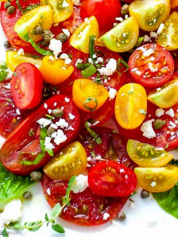 Overhead view of heirloom tomatoes arranged on a platter with feta cheese