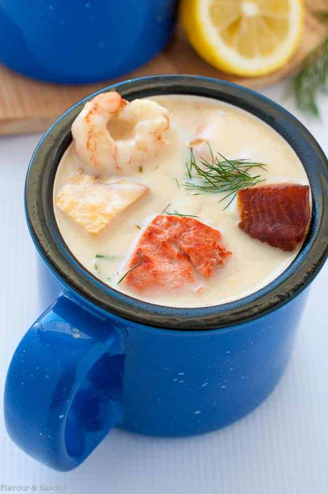 How to Make the Best Seafood Chowder. A blue soup mug of seafood chowder with smoked salmon, prawns, salmon and cod.