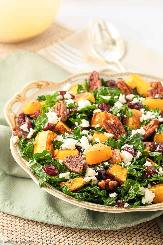 Butternut Squash Salad with Cranberries and Feta in a gold-rimmed dish on a green cloth