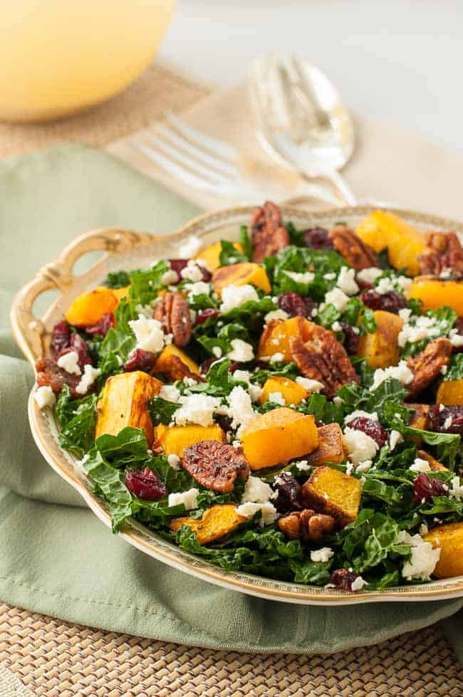 Butternut Squash Salad with Kale Cranberries + Feta in a gold-rimmed bowl