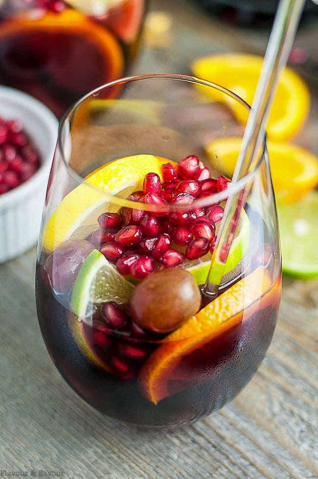 Pomegranate Red Wine Sangria in a glass with citrus fruit slices and pomegranate arils