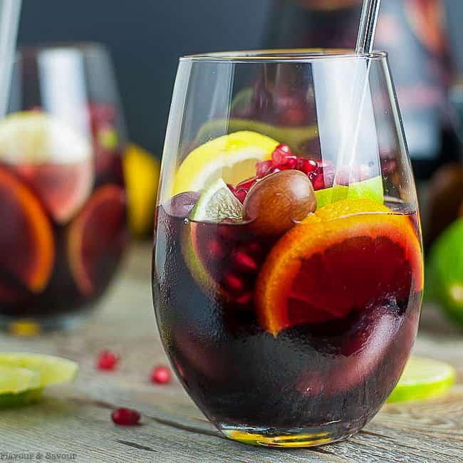 Side view of a glass of Pomegranate Red Wine Sangria with orange, lemon and lime slices