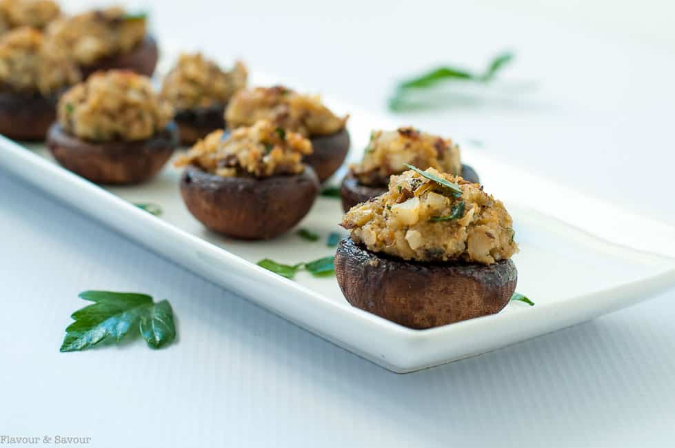Garlic Lovers' Blue Cheese Stuffed Mushrooms in a row on a white serving dish