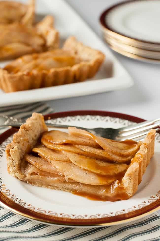 One serving of Gluten Free Cinnamon Pear Tart with Caramel Sauce on a china plate
