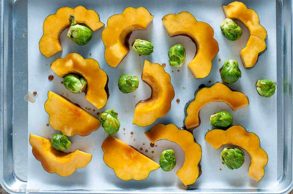 Half moon slices of acorn squash and Brussels Sprouts on a baking pan, tossed with a honey balsamic dressing, ready to make roasted acorn squash.