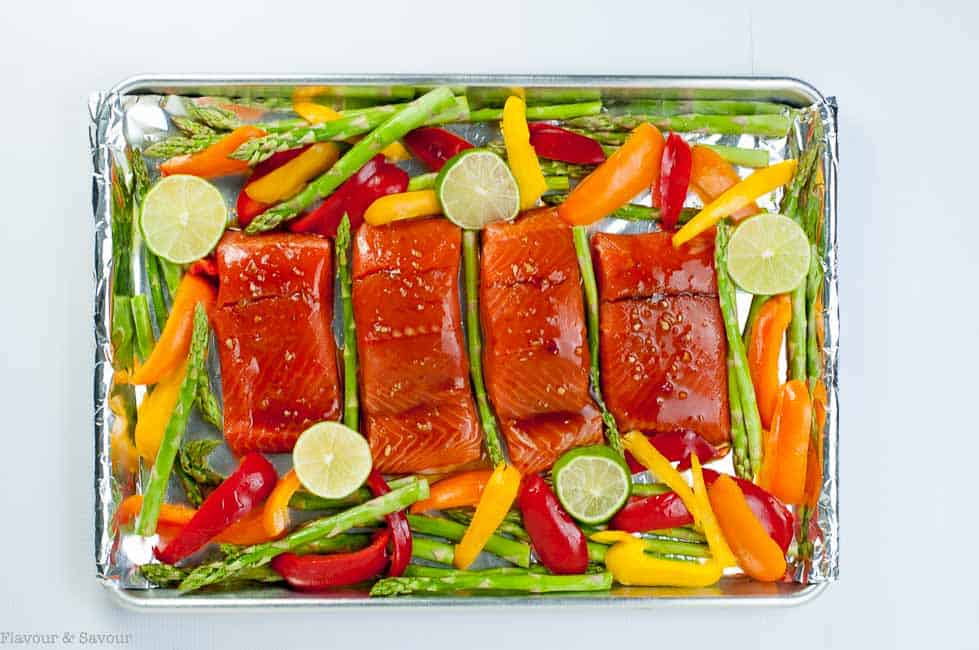 Raw Thai Chili Salmon fillets surrounded by raw asparagus spears and sliced bell peppers on a sheet pan.