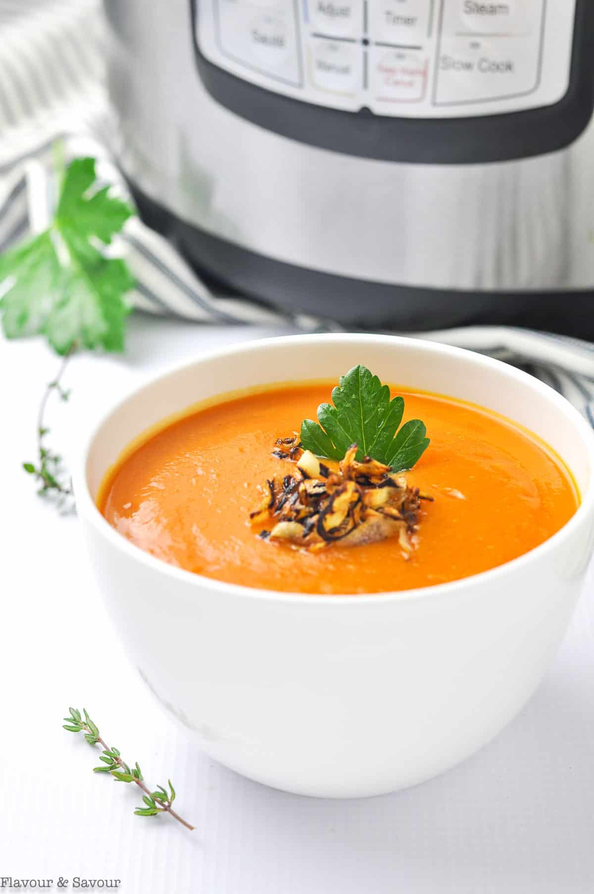 A bowl of Carrot Ginger Soup with garnishes.