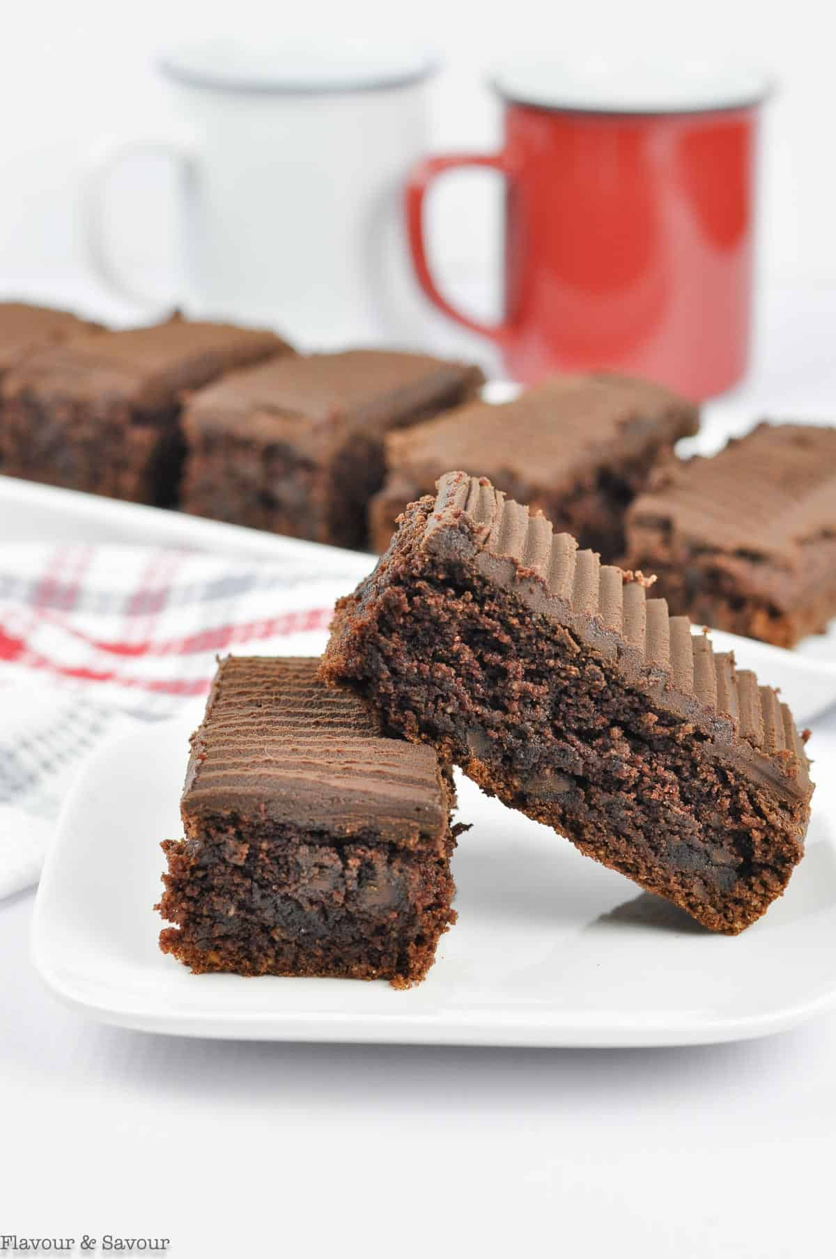 Two bars of Brownies on a plate with coffee cups in the background.