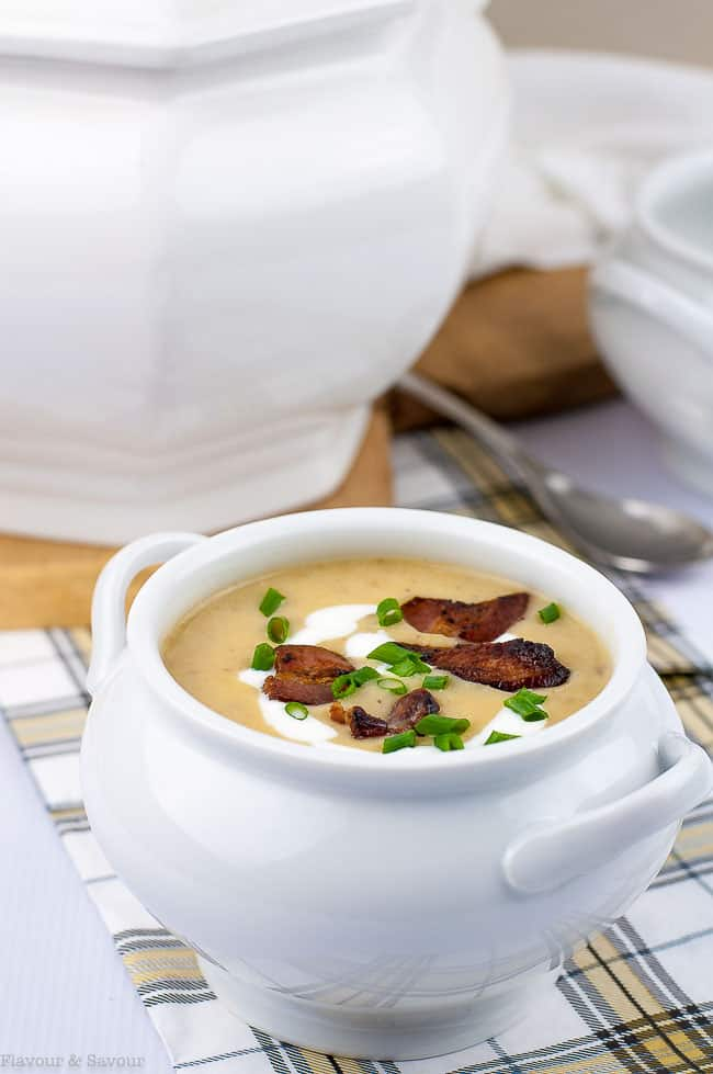 Instant Pot Potato Leek Soup with Bacon in a soup tureen garnished with bacon and chives