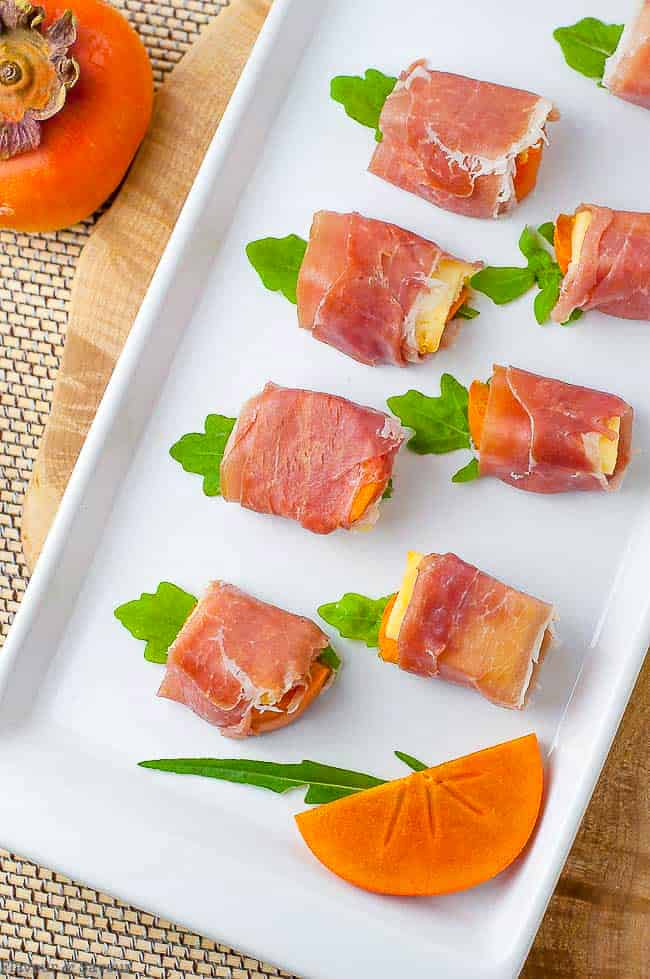 Overhead view of Persimmon Prosciutto Cheese Bites on a white platter