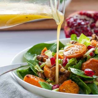 Pouring Dressing on Roasted Sweet Potato Salad with Maple Walnuts and Pomegranate