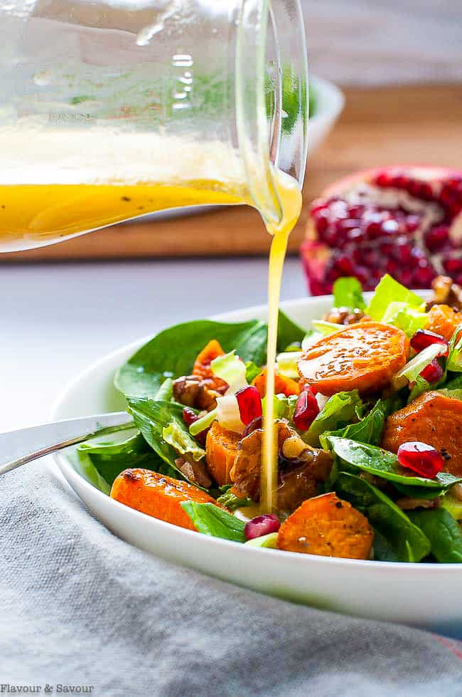 Pouring dressing on Roasted Sweet Potato Spinach Salad