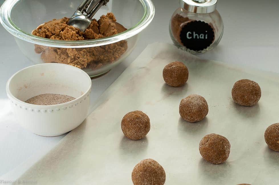Preparing Gluten-Free Chai Spiced Snickerdoodles by rolling and coating in cinnamon-sugar mix