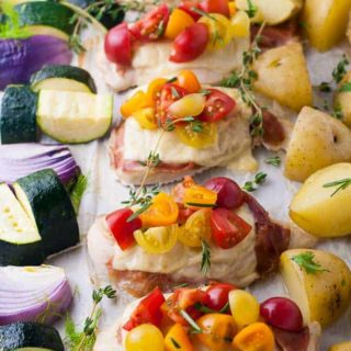 Prosciutto and Cheesy Chicken Sheet Pan Dinner baked on one pan and topped with cherry tomatoes and herbs.