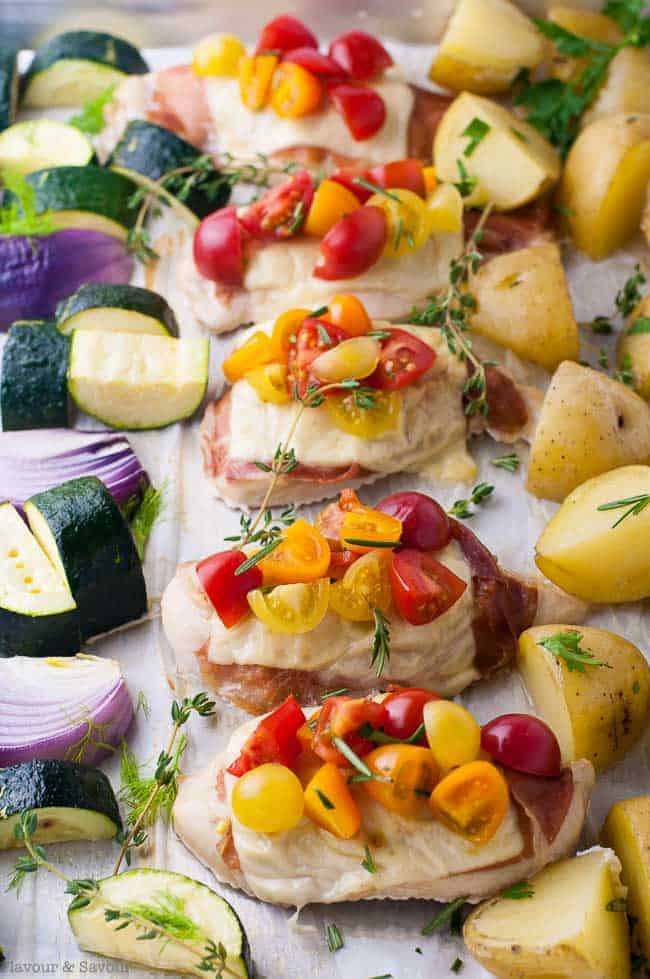 Prosciutto and Cheesy Chicken Sheet Pan Dinner showing chicken topped with cheese and cherry tomatoes surrounded by potatoes, zucchini and red onions.