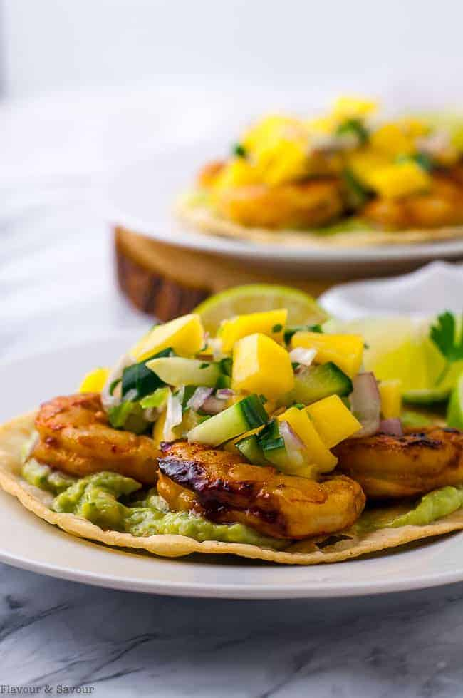 Chipotle Peach Shrimp Tostadas topped with guacamole, grilled shrimp and mango salsa