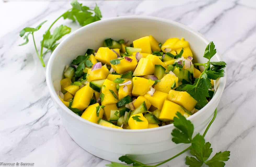 Mango Salsa in a bowl garnished with cilantro leaves