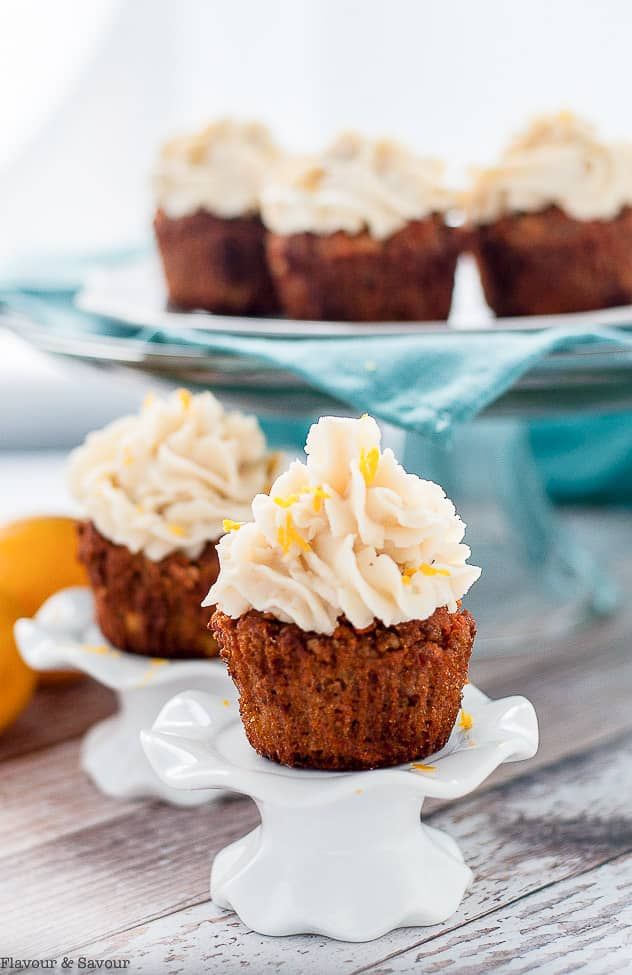 Two carrot cake cupcakes on cupcake pedestals
