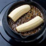 adding bananas to Caribbean Rum Bananas Flambé with Amaretto