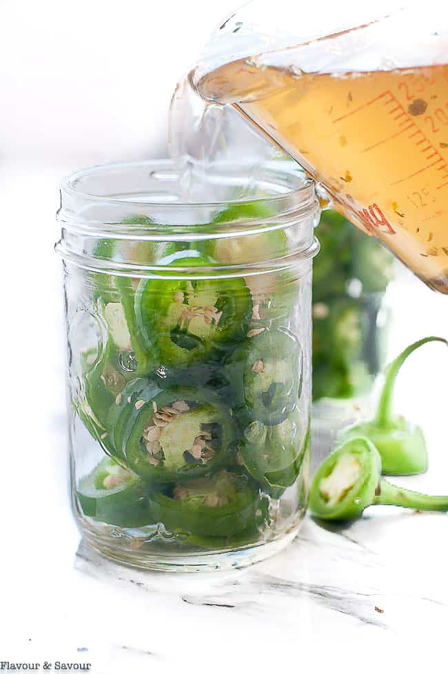 pouring pickling liquid into Mason jars with jalapeño pepper rings