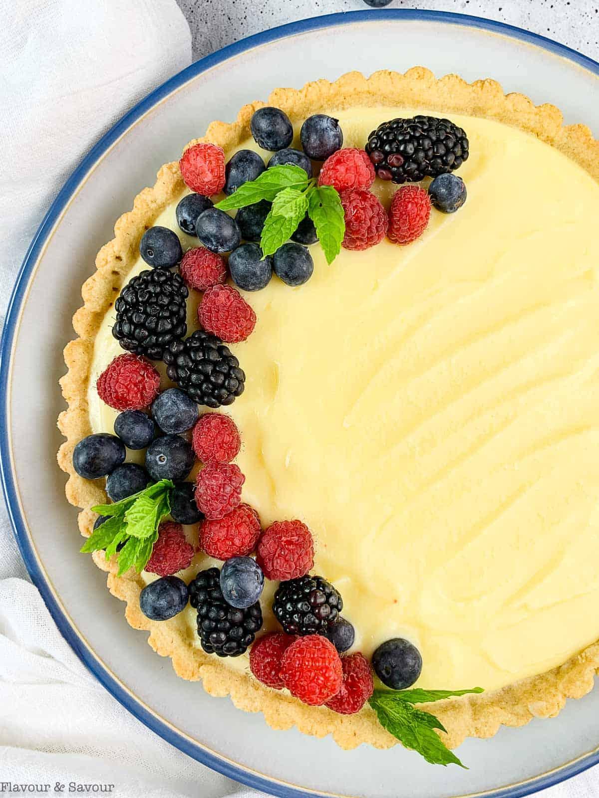 Overhead view of gluten-free lemon curd tart with fresh berries