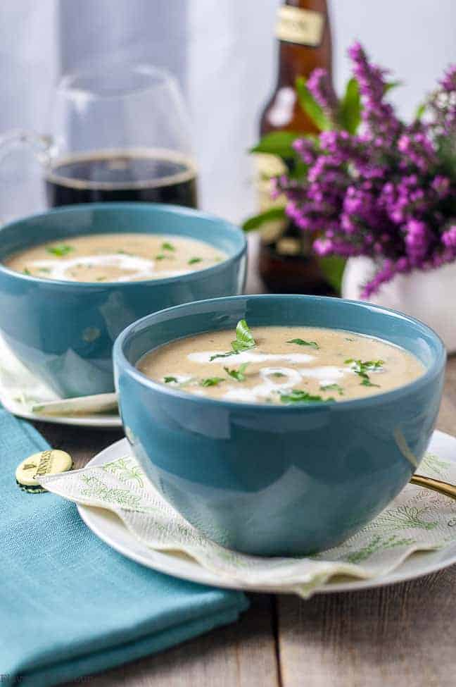 Creamy Roasted Garlic Irish Potato Soup in turquoise bowls with a mug of Guinness