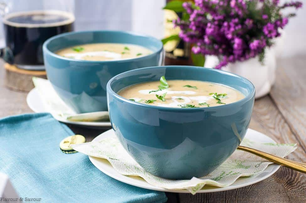 Creamy Roasted Garlic Irish Potato Soup in blue bowls