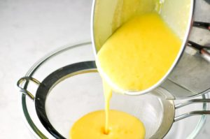Straining lemon curd through a sieve to make Lemon Curd Tart